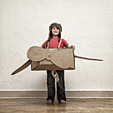 Proud little boy playing with pilot hat and cardboard box aeroplane - MMFF000406