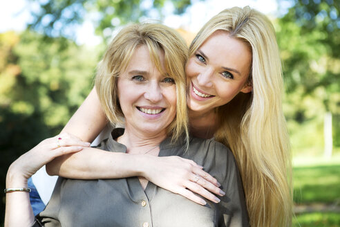 Portrait of smiling mother and adult daughter in park - GDF000527