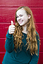 Portrait of smiling teenage girl with thumb up in front of red wooden wall - SARF000961