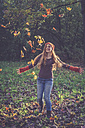 Teenage girl throwing autumn leaves - SARF000955