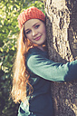 Portrait of smiling teenage girl hugging a tree - SARF000954