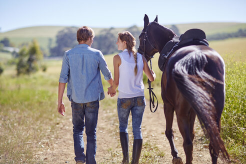 Young couple walking with horse on the countryside - ZEF001701