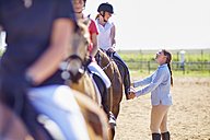 Coach and girls on horses on riding ring - ZEF001875