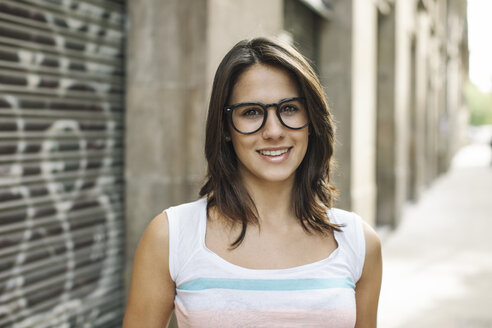 Portrait of smiling young woman wearing black glasses - EBSF000302