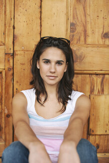 Portrait of young woman sitting in front of a wooden door - EBSF000328