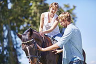 Young man with woman riding on horse - ZEF001735