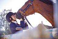 Smiling young woman with horse on show jumping course - ZEF001768