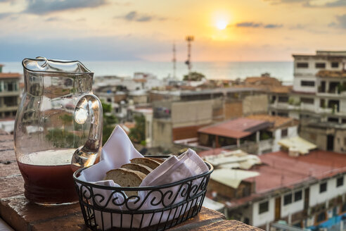 Mexico, Jalisco, View of Puerto Vallarta before sunset, Bread basket and carafe on balustrade - ABAF001540