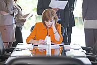 Businesswoman in conference room reading document - ZEF002232
