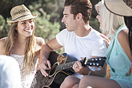 Happy friends with guitar outdoors - ZEF002441
