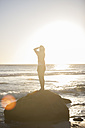 Young woman standing on rock on the beach at sunset - ZEF002484