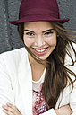 Portrait of young smiling woman with long brown hair wearing hat - UUF002347