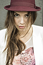 Portrait of young woman with long brown hair wearing hat - UUF002348