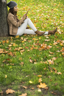 Young woman leaning against a tree using digital tablet - UUF002381