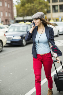 Young smiling woman with smartphone and wheeled luggage walking along a street - UUF002384