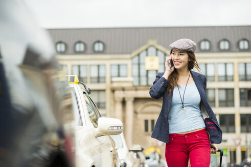 Young woman telephoning with smartphone walking along a street - UUF002386