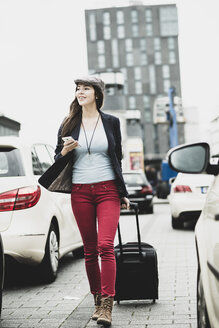 Young smiling woman with smartphone and wheeled luggage - UUF002390