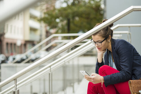 Young woman with sitting on stairs reading SMS - UUF002395