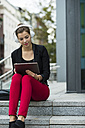 Young woman with headphones sitting on stairs using digital tablet - UUF002404