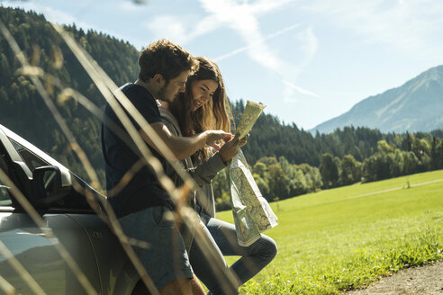 Austria, Tyrol, Tannheimer Tal, young coupe at car looking at map - UU002415