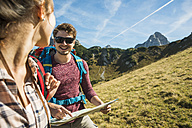Austria, Tyrol, Tannheimer Tal, young couple hiking with map - UUF002423