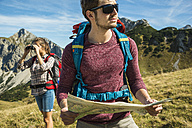 Austria, Tyrol, Tannheimer Tal, young couple hiking with map - UUF002425