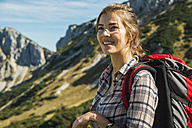 Austria, Tyrol, Tannheimer Tal, smiling young woman on hiking trip - UUF002442
