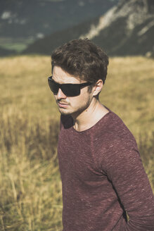 Austria, Tyrol, Tannheimer Tal, young man wearing sunglasses outdoors - UUF002446