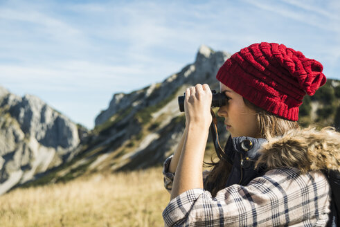Austria, Tyrol, Tannheimer Tal, young woman looking through binocular - UUF002447