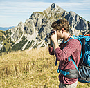 Austria, Tyrol, Tannheimer Tal, young man taking picture on alpine meadow - UUF002450