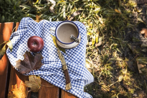 Coffee, apple and autumn leaves on wooden bench - SBDF001392