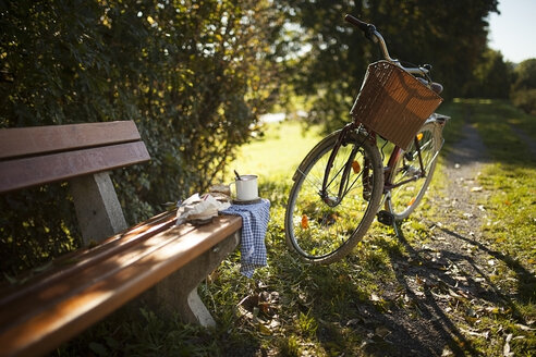 Bicycle next to on wooden bench - SBDF001396