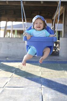 Smiling baby girl sitting on blue baby swing - SHKF000050