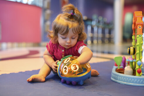 Baby girl playing with toys in a playroom of cruise liner - SHKF000080