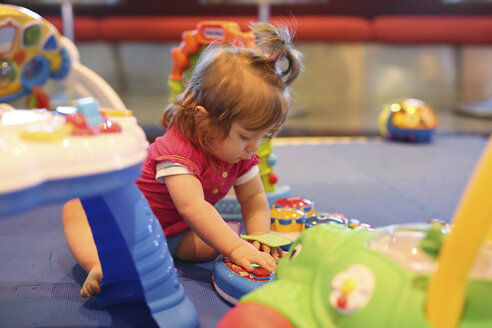 Baby girl playing with toys in a playroom of cruise liner - SHKF000099