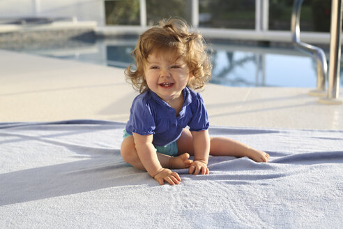 Portrait of baby girl sitting on a towel in front of swimming pool - SHKF000058