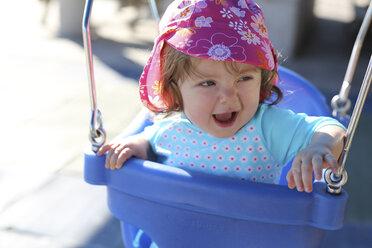 Portrait of baby girl sitting on blue baby swing - SHKF000065
