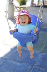 Smiling baby girl sitting on blue baby swing - SHKF000066