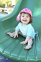 Smiling baby girl on green shute - SHKF000068