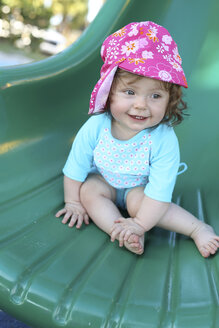 Smiling baby girl on green shute - SHKF000069