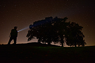 Germany, Bavaria, Allgaeu, Fuessen, man at night with torchlight under starry sky - FD000085