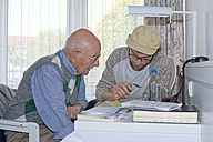 Young and old man completing form together - LAF001181
