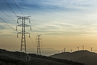 Spain, Andalusia, Tarifa, Wind farm and power pylons in the evening light - KBF000243