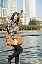 Germany, Frankfurt, young businesswoman by the riverside with cell phone - UUF002487