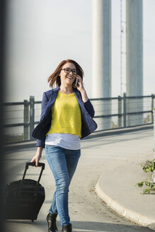 Smiling young woman with baggage on cell phone - UUF002511