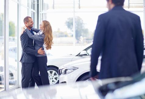 Couple hugging at car dealer - ZEF002019