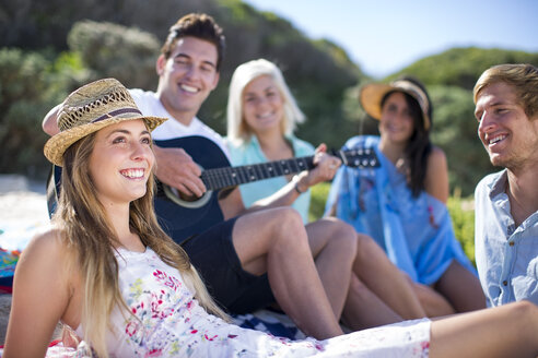 Friends socializing on the beach and playing acoustic guitar - ZEF002374