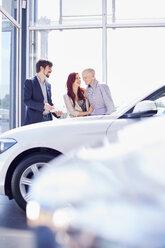 Car dealer with couple in showroom - ZEF002023