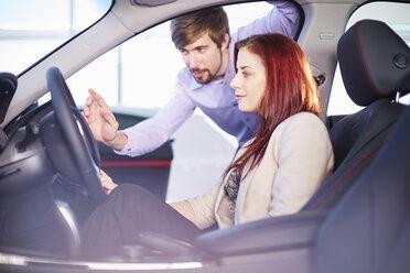 Car dealer talking to client inside car - ZEF002036