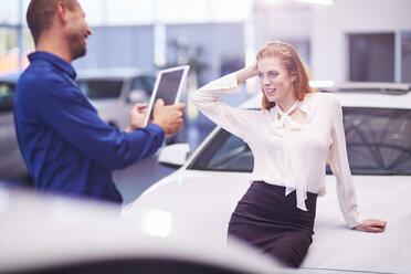 Woman at car dealer posing on bonnet for a photo - ZEF002060